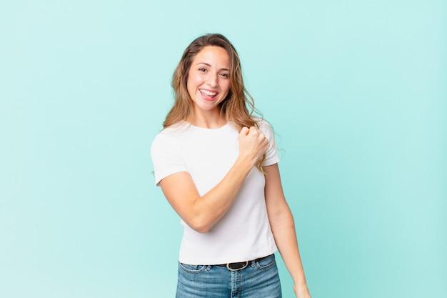 Ładna kobieta czuje się szczęśliwa i staje przed wyzwaniem lub świętuje