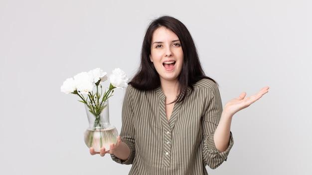 Ładna kobieta czuje się szczęśliwa i zdumiona czymś niewiarygodnym i trzyma ozdobne kwiaty. asystent agenta z zestawem słuchawkowym