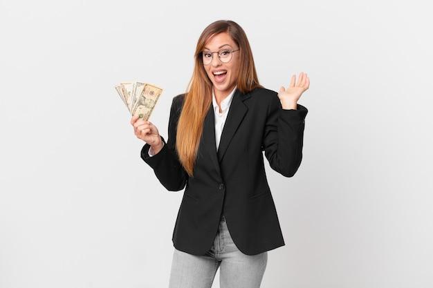 Ładna kobieta czuje się szczęśliwa i zdumiona czymś niewiarygodnym. koncepcja biznesu i dolarów