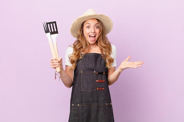 Ładna kobieta czuje się szczęśliwa i zdumiona czymś niewiarygodnym. koncepcja szefa kuchni z grilla