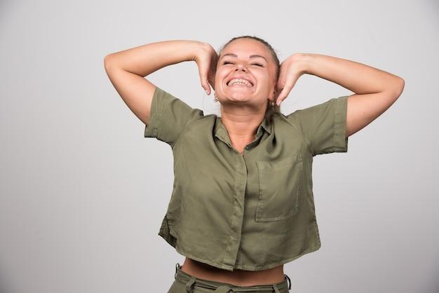 Ładna kobieta czuje się szczęśliwa na szarej ścianie.