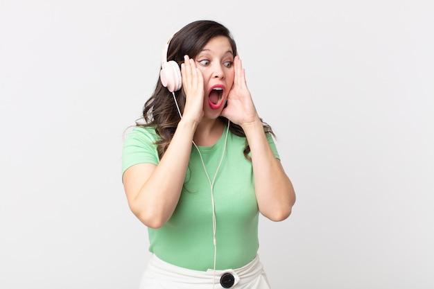 Ładna kobieta czuje się szczęśliwa, podekscytowana i zaskoczona słuchając muzyki przez słuchawki