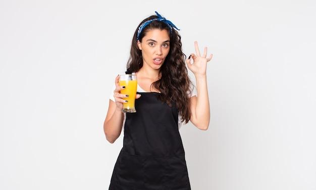 Ładna kobieta czuje się szczęśliwa, pokazując aprobatę dobrym gestem i trzymająca szklankę soku pomarańczowego