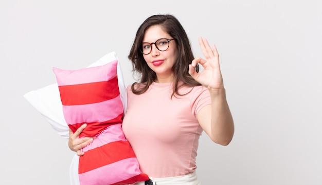 Ładna kobieta czuje się szczęśliwa, pokazując aprobatę dobrym gestem, ubrana w piżamę i trzymająca poduszkę