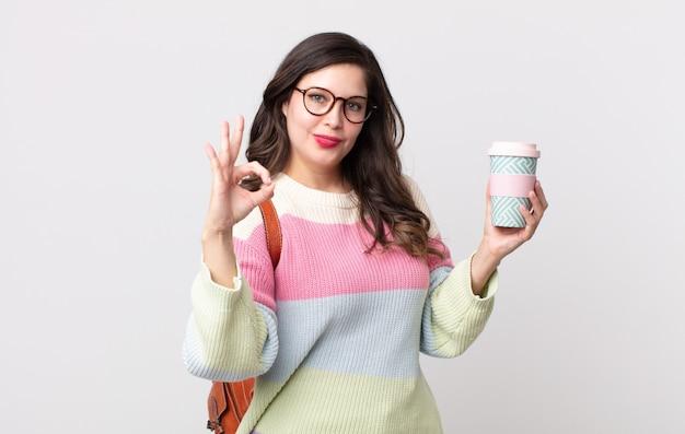 Ładna kobieta czuje się szczęśliwa, pokazując aprobatę w porządku gestem. koncepcja studenta