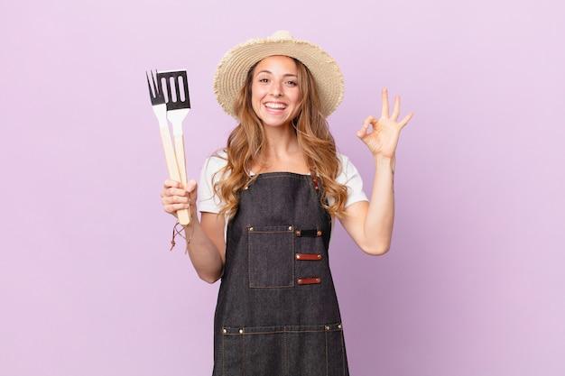 Ładna kobieta czuje się szczęśliwa, pokazując aprobatę w porządku gestem. koncepcja szefa kuchni z grilla
