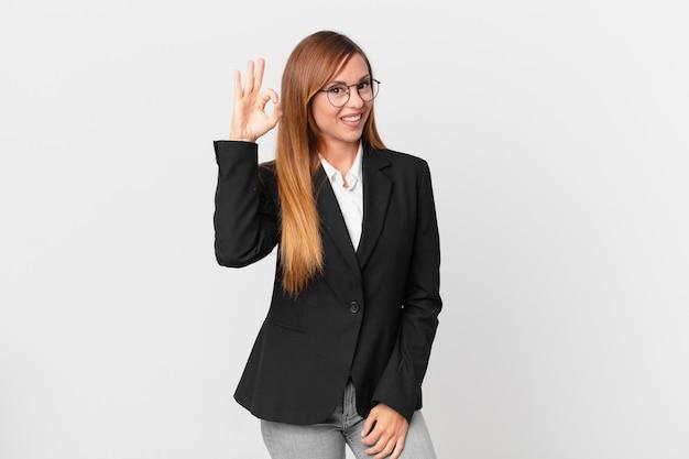 Ładna kobieta czuje się szczęśliwa, pokazując aprobatę w porządku gestem. pomysł na biznes
