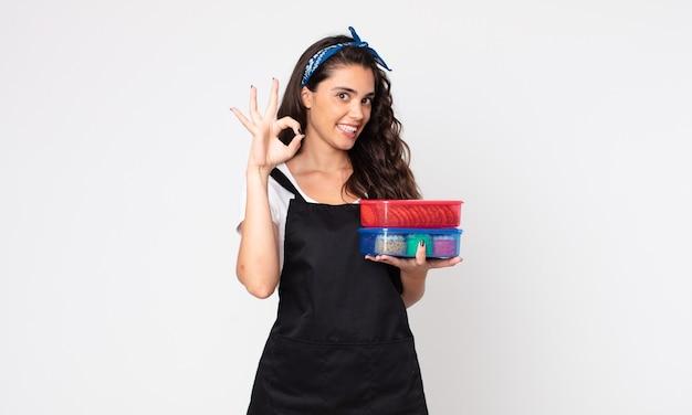 Ładna kobieta czuje się szczęśliwa, pokazuje aprobatę dobrym gestem i trzyma tupperware z jedzeniem