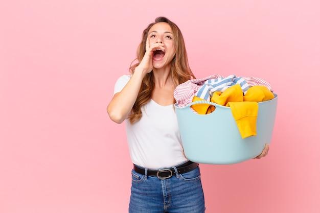 Ładna kobieta czuje się szczęśliwa, wydając wielki okrzyk z rękami przy ustach i praniem ubrań.