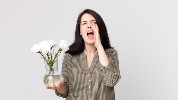 Ładna kobieta czuje się szczęśliwa, wydając wielki okrzyk z rękami przy ustach i trzymając ozdobne kwiaty. asystent agenta z zestawem słuchawkowym