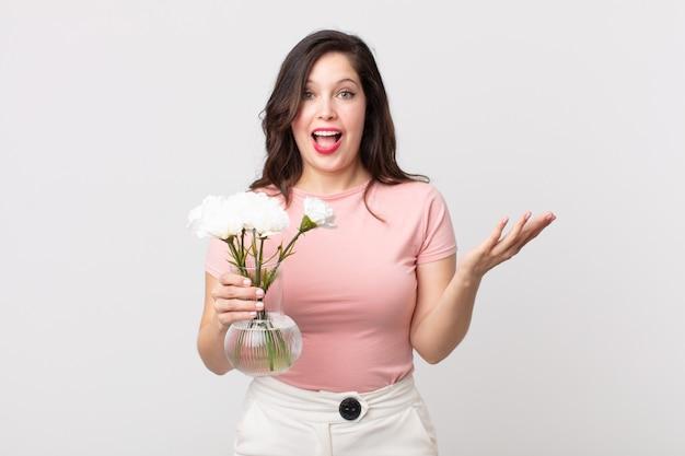 Ładna kobieta czuje się szczęśliwa, zaskoczona, gdy realizuje rozwiązanie lub pomysł i trzyma ozdobną doniczkę z kwiatami