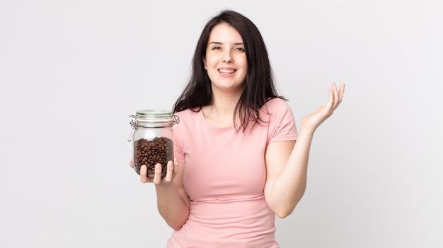 Ładna kobieta czuje się szczęśliwa, zaskoczona, gdy zdaje sobie sprawę z rozwiązania lub pomysłu i trzyma butelkę ziaren kawy