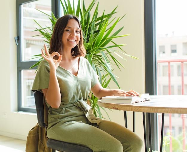 Ładna kobieta czuje się szczęśliwa, zrelaksowana i usatysfakcjonowana, okazując aprobatę dobrym gestem, uśmiechając się