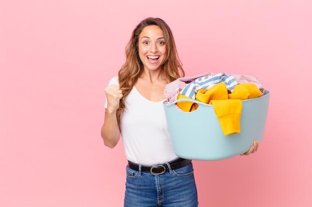 Ładna kobieta czuje się w szoku, śmieje się i świętuje sukces i pranie.