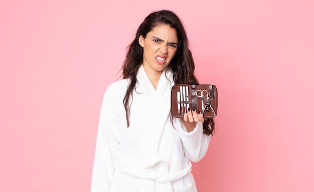 Ładna kobieta czuje się zakłopotana i zdezorientowana, trzymając kosmetyczkę z narzędziami do paznokci