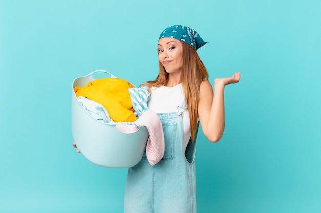 Ładna kobieta czuje się zakłopotana, zdezorientowana i wątpi, trzymając kosz do prania