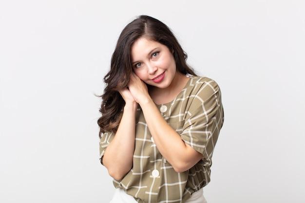 Ładna kobieta czuje się zakochana i wygląda słodko, uroczo i szczęśliwie, uśmiechając się romantycznie z rękami przy twarzy