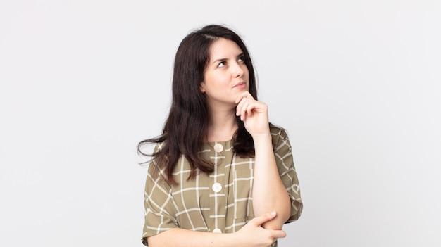 Ładna kobieta czuje się zamyślona, zastanawia się lub wyobraża sobie pomysły, marzy i patrzy na kopiowanie przestrzeni