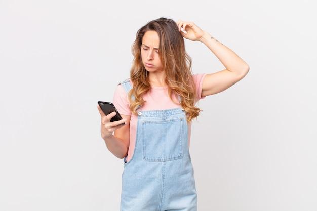 Ładna kobieta czuje się zdezorientowana i zdezorientowana, drapiąc się po głowie i trzymając smartfon