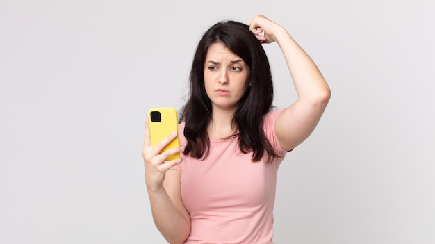 Ładna kobieta czuje się zdezorientowana i zdezorientowana, drapiąc się po głowie smartfonem