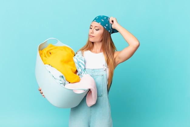 Ładna kobieta czuje się zdezorientowana i zdezorientowana, drapiąc się po głowie, trzymająca kosz do prania