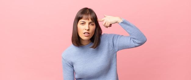 Ładna kobieta czuje się zdezorientowana i zdezorientowana, pokazując, że jesteś szalona, szalona lub oszalała