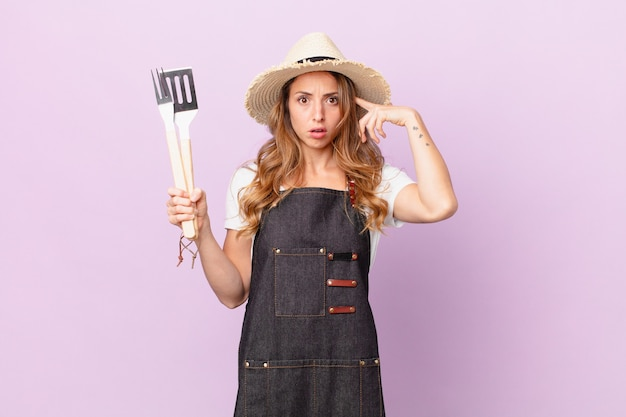 Ładna kobieta czuje się zdezorientowana i zdezorientowana, pokazując, że jesteś szalony. koncepcja szefa kuchni z grilla