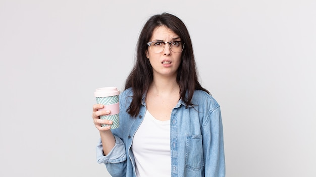 Ładna kobieta czuje się zdezorientowana i zdezorientowana, trzymając kawę na wynos