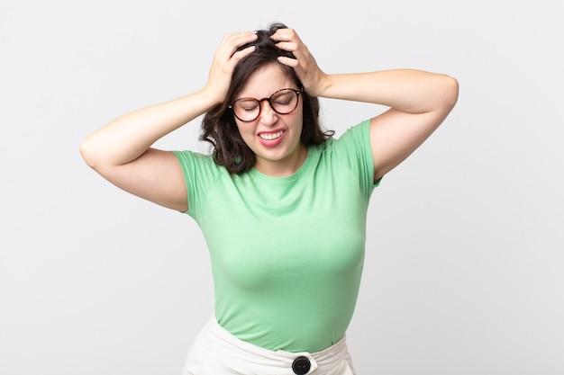 Ładna kobieta czuje się zestresowana i sfrustrowana, podnosi ręce do głowy, czuje się zmęczona, nieszczęśliwa i ma migrenę
