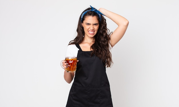 Ładna kobieta czuje się zestresowana, niespokojna lub przestraszona, z rękami na głowie i trzymającą kufel piwa