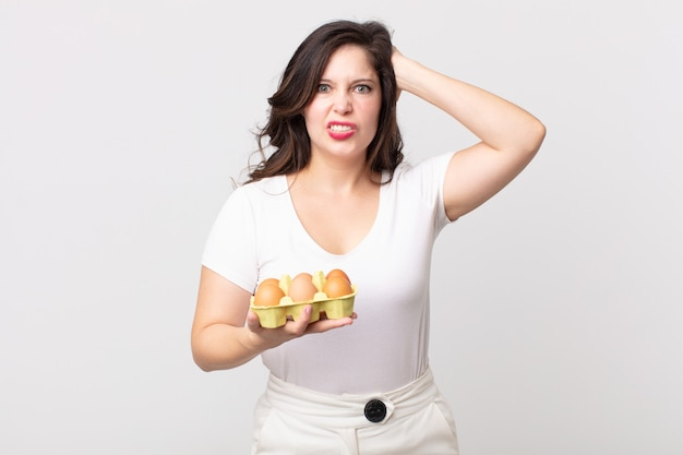 Ładna kobieta czuje się zestresowana, niespokojna lub przestraszona, z rękami na głowie i trzymająca pudełko z jajkami