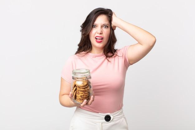 Ładna kobieta czuje się zestresowana, niespokojna lub przestraszona, z rękami na głowie i trzymająca szklaną butelkę po ciastkach