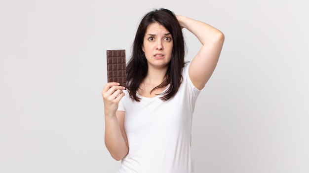 Ładna kobieta czuje się zestresowana, niespokojna lub przestraszona, z rękami na głowie i trzymająca tabliczkę czekolady
