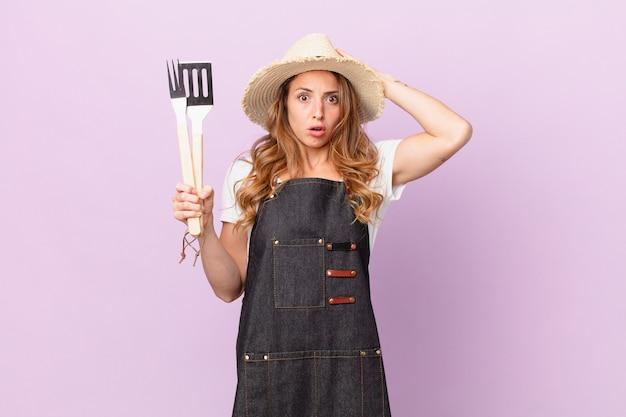 Ładna kobieta czuje się zestresowana, niespokojna lub przestraszona, z rękami na głowie. koncepcja szefa kuchni z grilla