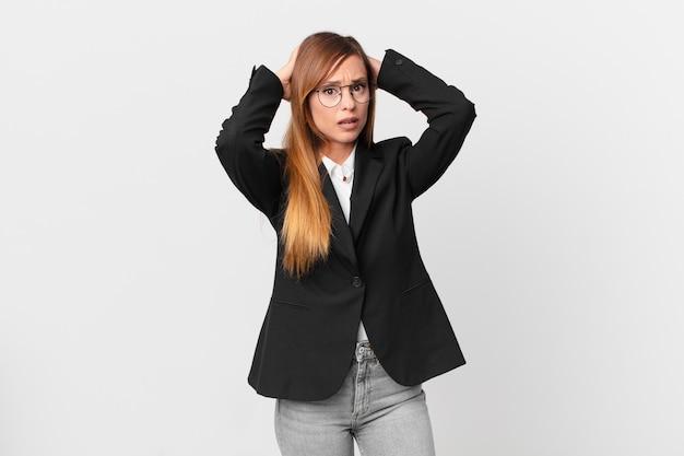 Ładna kobieta czuje się zestresowana, niespokojna lub przestraszona, z rękami na głowie. pomysł na biznes