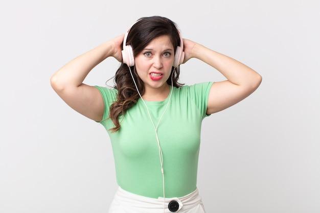 Ładna kobieta czuje się zestresowana, niespokojna lub przestraszona, z rękami na głowie słucha muzyki przez słuchawki