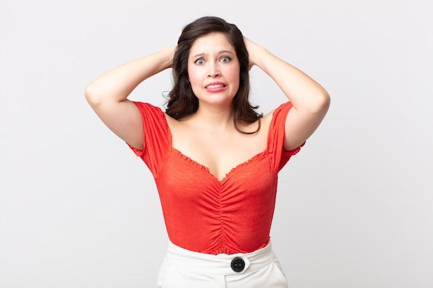 Ładna kobieta czuje się zestresowana, zmartwiona, niespokojna lub przestraszona, z rękami na głowie, panikująca z powodu błędu