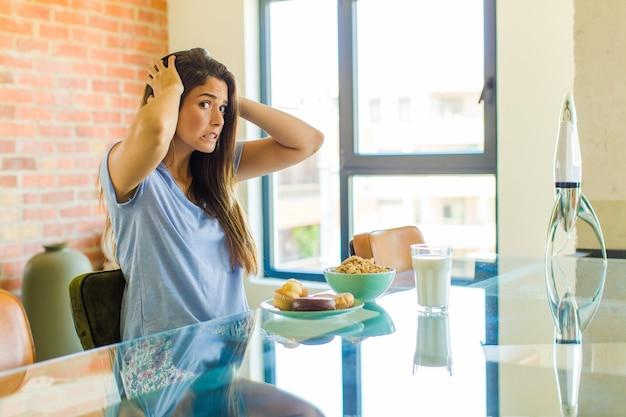 Ładna kobieta czuje się zestresowana, zmartwiona, niespokojna lub przestraszona, z rękami na głowie, panikuje podczas pomyłki