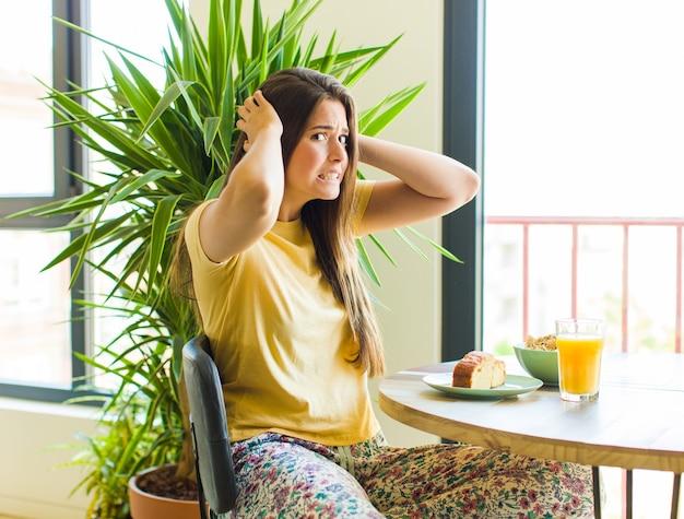 Ładna kobieta czuje się zestresowana, zmartwiona, niespokojna lub przestraszona, z rękami na głowie