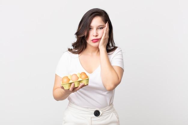 Ładna kobieta czuje się znudzona, sfrustrowana i senna po męczącym i trzymającym pudełko jaj