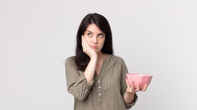 Ładna kobieta czuje się znudzona, sfrustrowana i senna po męczącym trzymaniu pustej miski. asystent agenta z zestawem słuchawkowym