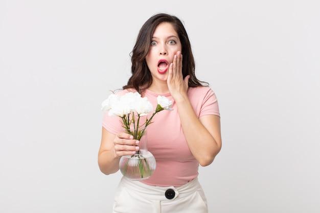 Ładna kobieta czuje się zszokowana i przestraszona i trzyma ozdobną doniczkę z kwiatami
