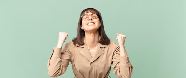 Ładna kobieta czuje się zszokowana, podekscytowana i szczęśliwa, śmieje się i świętuje sukces, mówiąc wow!