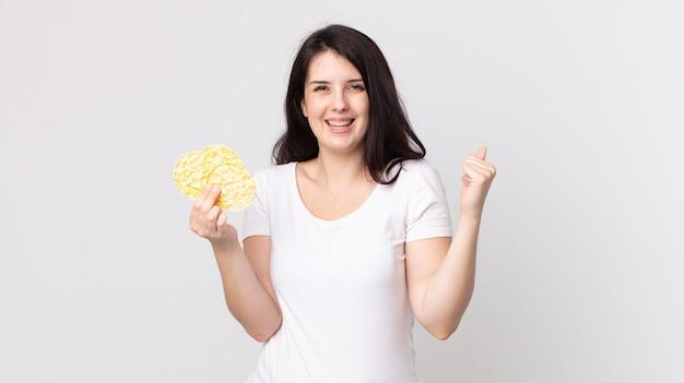 Ładna kobieta czuje się zszokowana, śmiejąc się i świętując sukces i trzymając dietetyczne ciastka ryżowe