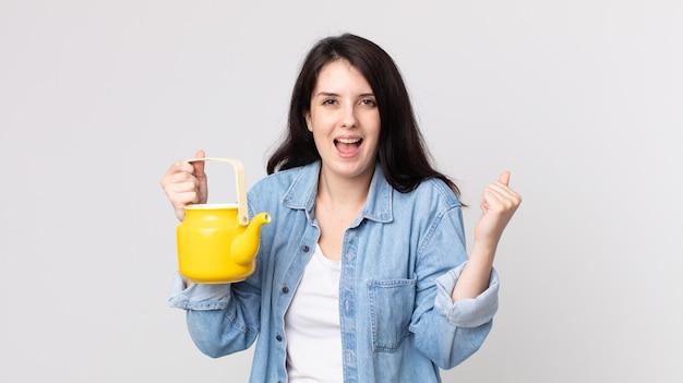 Ładna kobieta czuje się zszokowana, śmieje się i świętuje sukces i trzyma czajniczek