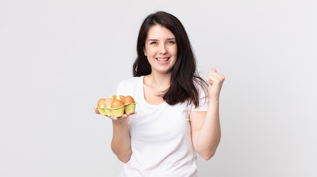 Ładna kobieta czuje się zszokowana, śmieje się i świętuje sukces i trzyma pudełko z jajkami
