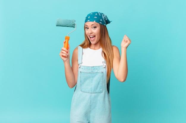 Ładna kobieta czuje się zszokowana, śmieje się i świętuje sukces, malując nową ścianę domu