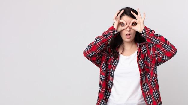Ładna kobieta czuje się zszokowana, zdumiona i zaskoczona, trzymająca okulary ze zdumionym, niedowierzającym spojrzeniem