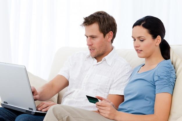 Ładna kobieta czytania kodu na karcie kredytowej dla swojego chłopaka