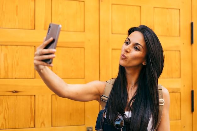 Ładna kobieta dmuchanie pocałunek biorąc selfie zdjęcie młoda dziewczyna zrobić autoportret na zewnątrz.